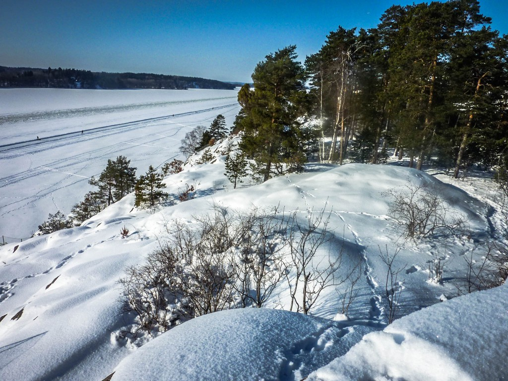 Looking down over a frozen lake that has become a ski track
