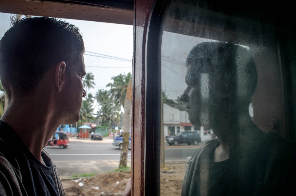 Watching the world go by from the open door of  Sri Lankan train.